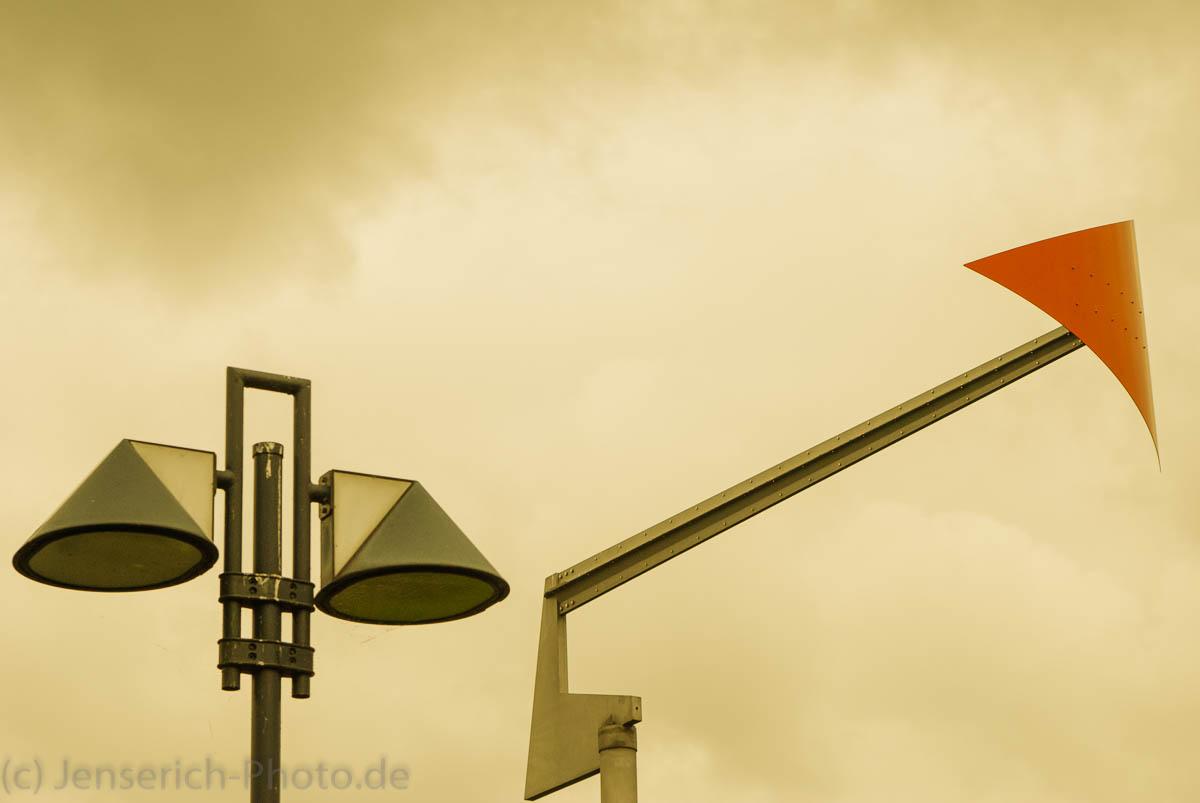 Farbakzent an einem Windrichtungsanzeiger mit einer Laterne im Hintergrund
