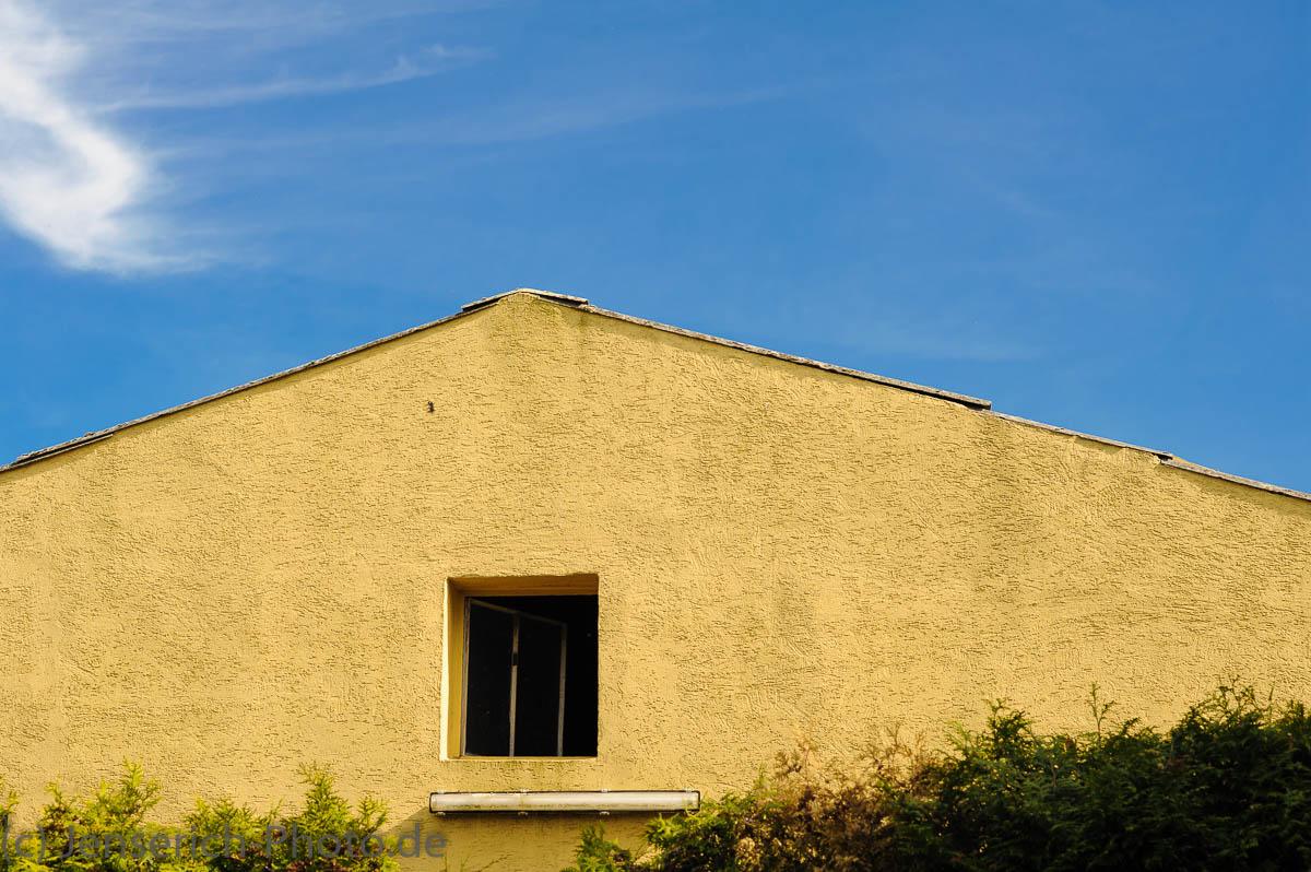 Gelber Hausgiebel vor blauem Himmel