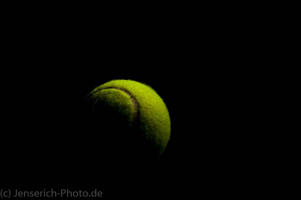Ein gelber Tinnisball mit einem externen Blitz beleuchtet